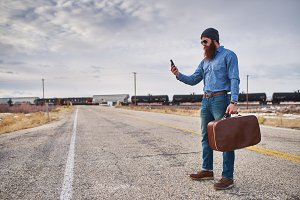 bearded traveler checking phone