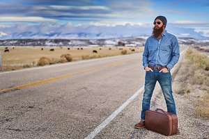 bearded hitchhiker waiting by road