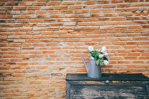 Beautiful vase of flowers on aged cupboard in red vintage brick wall background