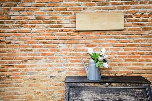 Beautiful vase of flowers on aged cupboard in red vintage brick wall background with empty wood board sign