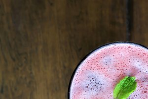 Top view of pink and red smoothie over wooden background with copy space