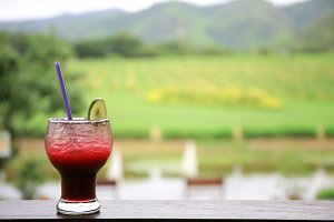 Glass of iced cocktail in winery vineyard hill in background
