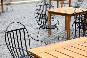 Empty chairs in outdoor restaurant with beautiful European style architecture tiles (selective focus)