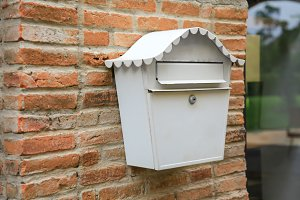 Vintage white mail box hanging on red brick wall (selective focus)