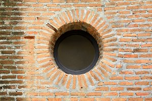 Vintage circular shape window on red brick wall architecture