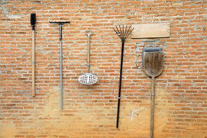 Agriculture and farming working tools hanging on red vintage brick wall (selective focus)