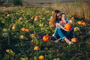 Mom and daughter on pumpkins field