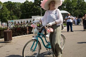 Lady in a broad hat on a bicycle