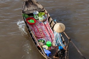 Woman on boat floating down Mekong