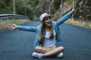 girl sitting on the road having fun and celebrating