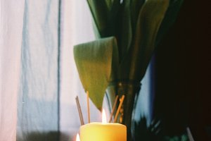 Lit candles with red tulips