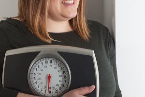 Smiling woman holding bathroom scale