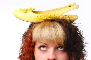 woman with yellow shoe on her head