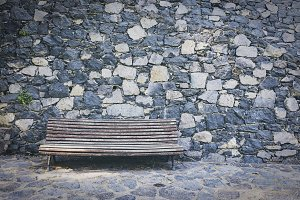 Old wooden bench against a stone wall