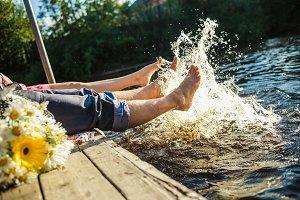 Couple legs in the water splashing