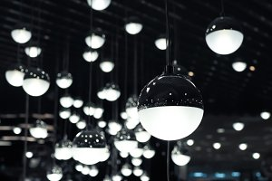 Set of white fluoescent round light bulbs hanging on decorative ceiling