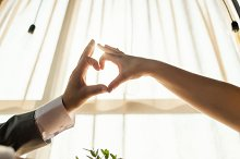 Female and male hands forming a heart shape with sunlight at restaurant interior. Concept of love, wedding.