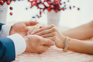 groom holding bride's hands with ring at table