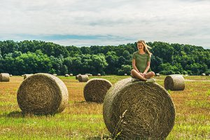 Young blond lady sitting on haystack