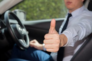 Happy man in casual suit giving thumbs up to someone in the car