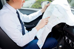 Young man lost direction and looking at map in car to plan his journey