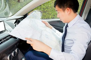 Young Asian man lost way and looking at the map to find ways out