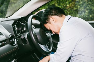 Sleeping & tired businessman with fatigue on  steering wheel in car