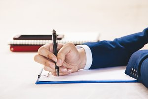 Closeup of Businessman writing on paper on notepad