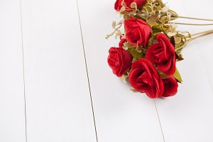 Red rose laying on white wooden background