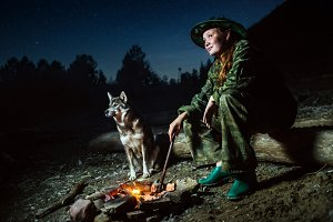 tourist girl with her dog around campfire at night with stars.
