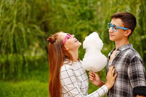 Enamoured teens eat cotton candy.
