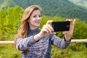 woman is doing selfie on her phone