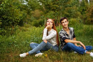 Couple teens sitting on the lawn
