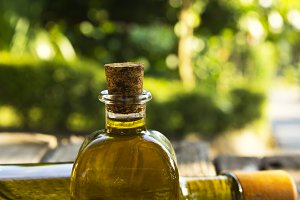 bottles of olive oil on wood with green background