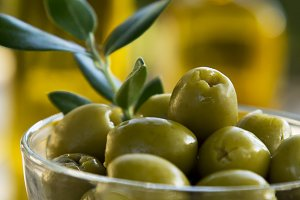 glass cup full of olives with green background