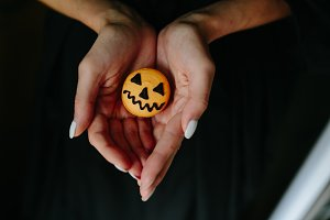 woman holding a biscuit for Halloween