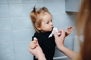 Mother feed her daughter with a spoon