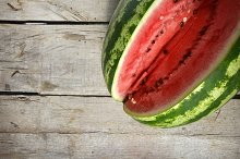 Summer and fresh watermelon theme: a man holds a slice of watermelon on a green background