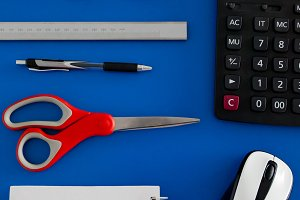 Flat lay top view of office supply, IT equipment, notebook placing over blue background