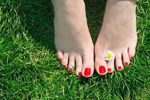 Woman feet on green grass