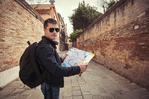 tourist man walking with a map