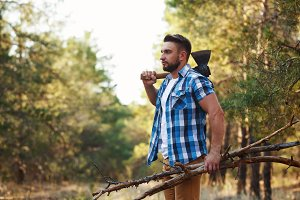 Lumberjack with an ax in forest