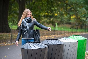 Woman throws recycle paper in trash