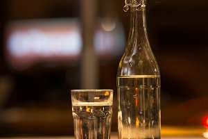 Glass of water and restaurant bottle