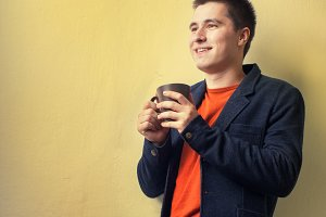 man drinking coffee near the wall