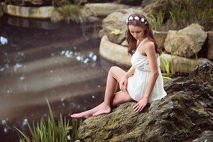 romantic girl sitting near the lake