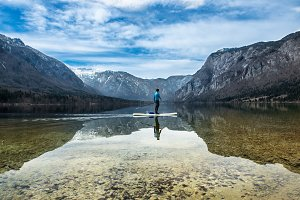 man on a canoe on a mountain lake