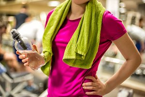 Woman holding water in gym
