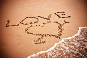 inscription LOVE on beach sand