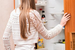 Young woman in looking to the fridge